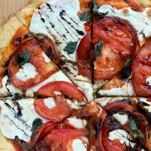 caprese pizza with balsamic glaze, sliced