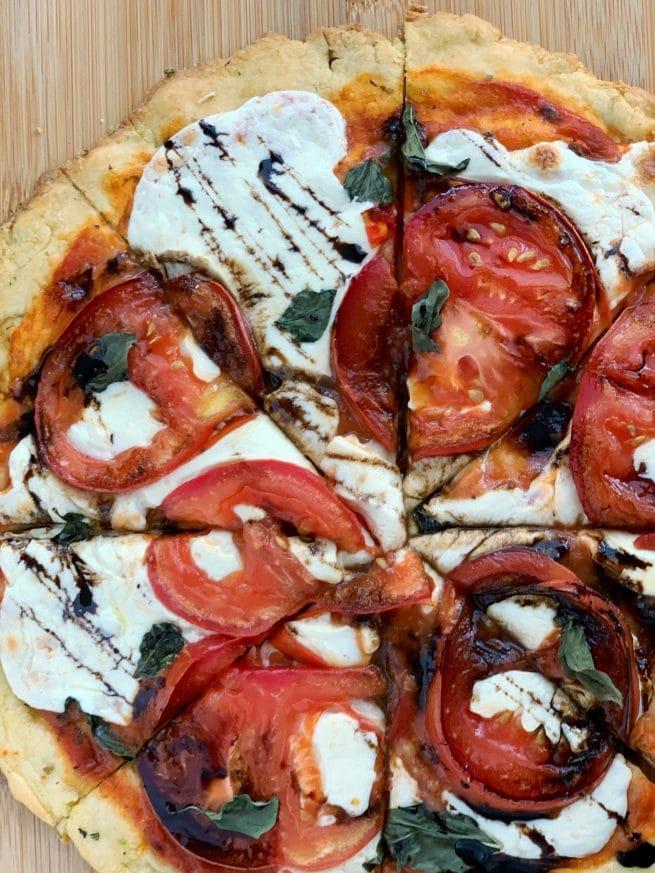 caprese pizza with balsamic glaze, sliced