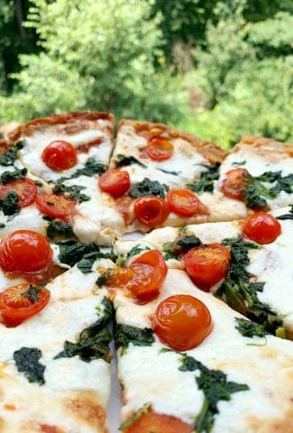 closeup shot of personal pan pizza with cherry tomatoes and spinach