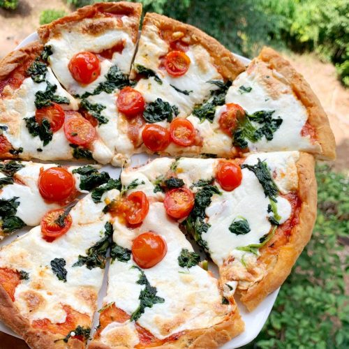 overhead shot of personal pan pizza with spinach and tomatoes