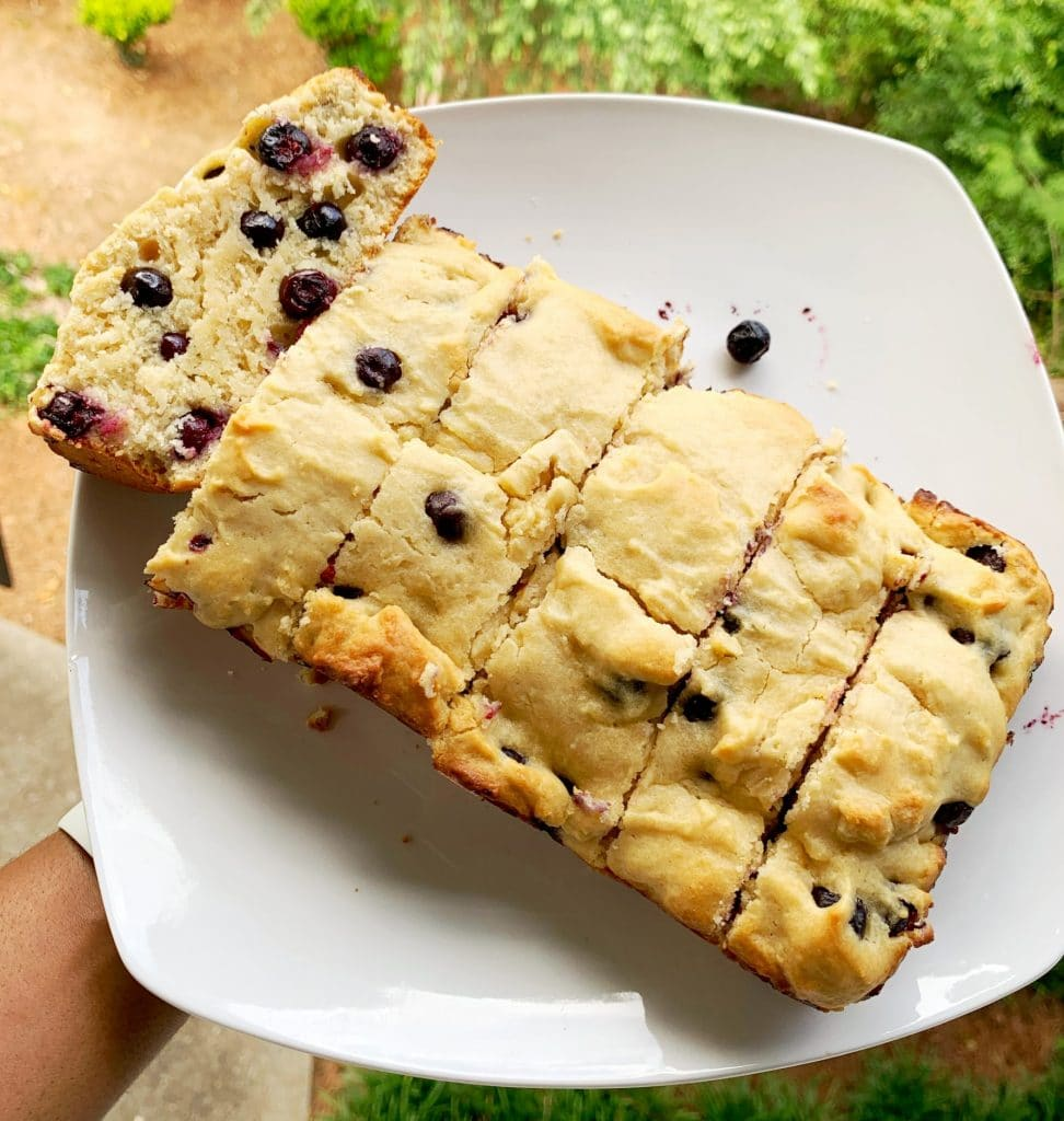 overhead shot of lemon blueberry bread loaf on a white plate