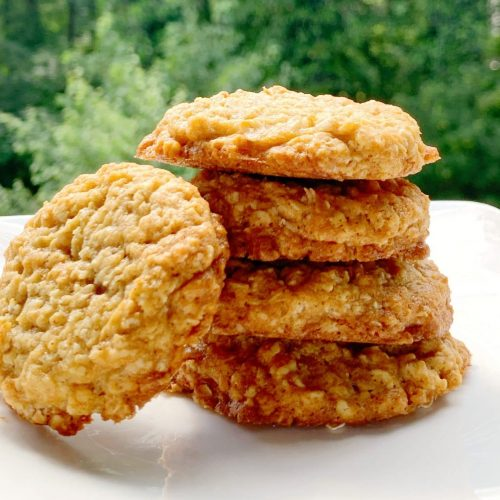 picture of chewy oatmeal cookies stacked on a white plate