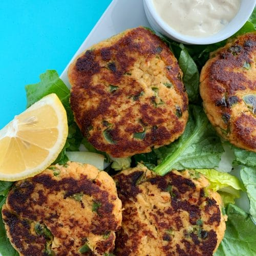 picture of multiple salmon cakes on a bed of lettuce with a lemon