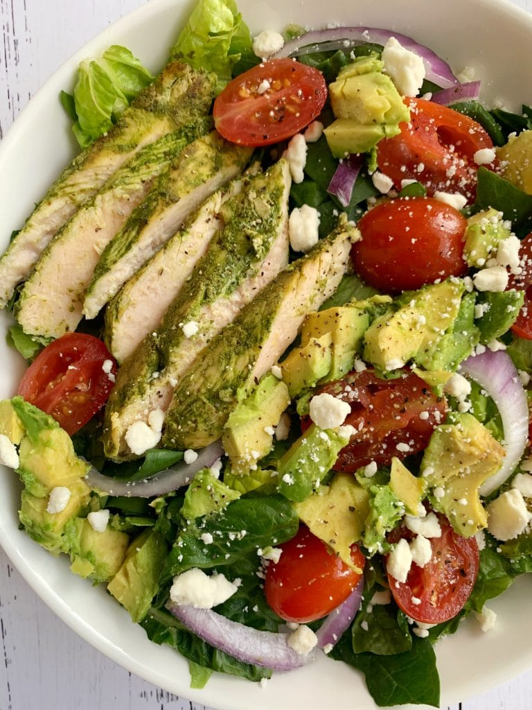 closesup of pesto chicken and avocado salad with feta cheese and red onions