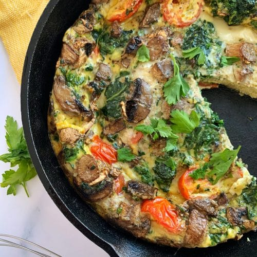 cast iron veggie frittata with a slice cut out and parsley on the side