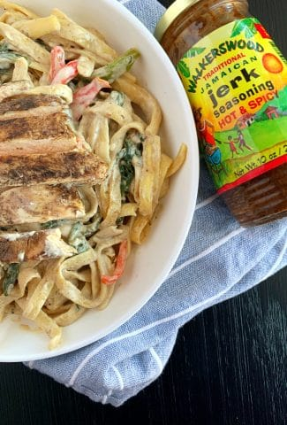 jerk chicken pasta in a white bowl with jerk seasoning on the side