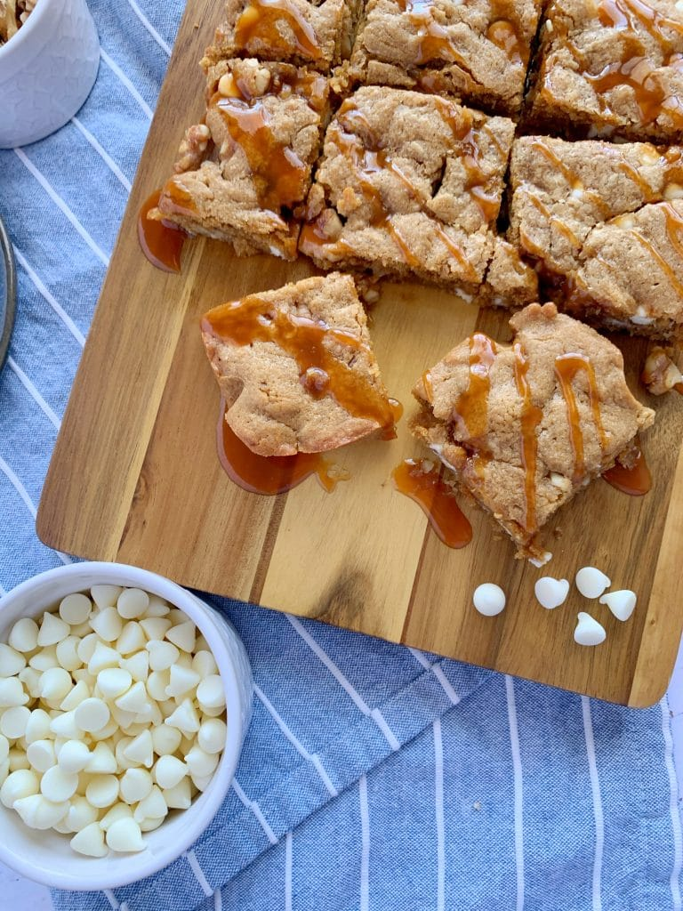 blondies drizzled with caramel on a wooden board with white chocolate chips