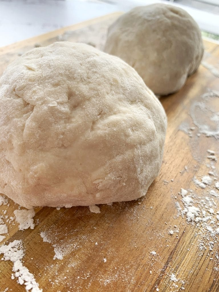 ball of pizza dough on wooden board with homemade pizza dough in the background
