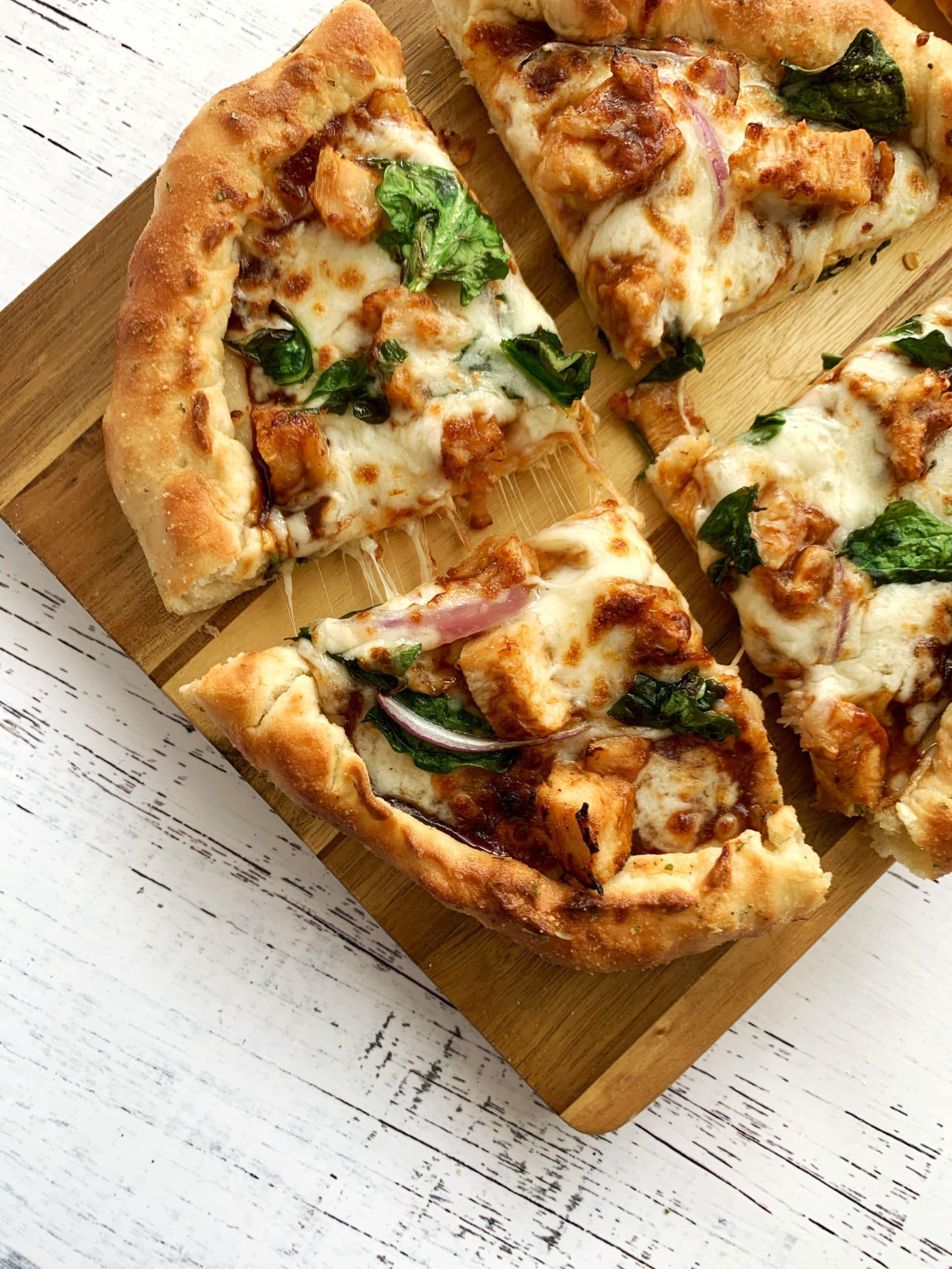 BBQ chicken pizza on a wooden slab