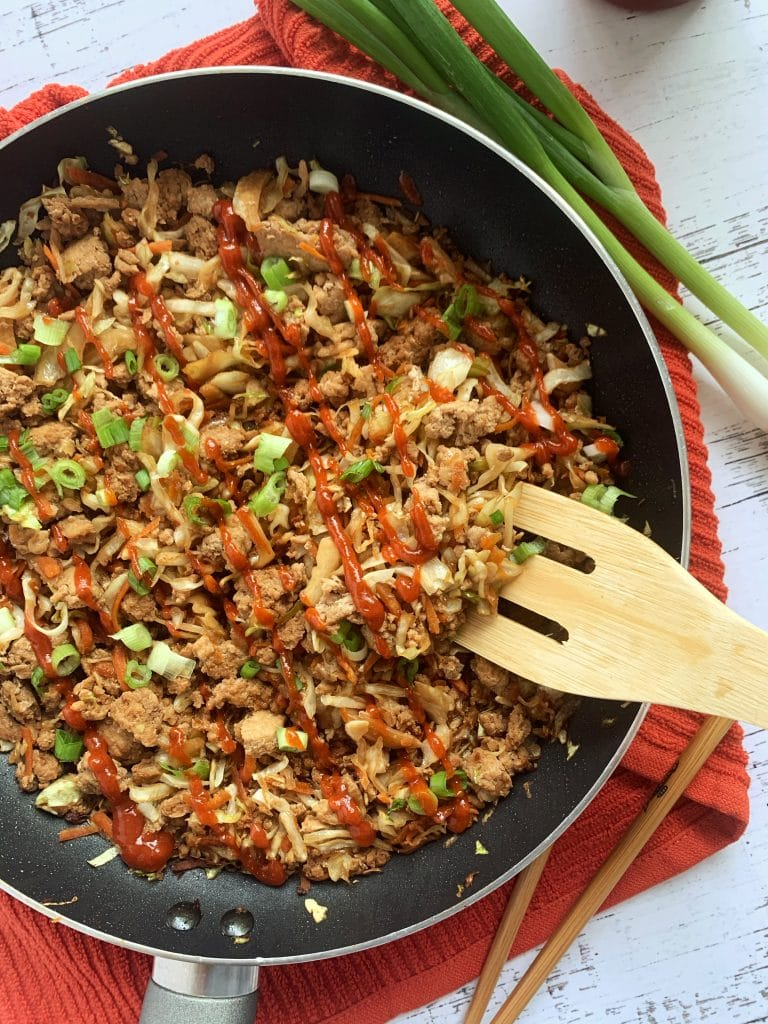 egg roll filling in a skillet with green onions and a flat wooden spatula