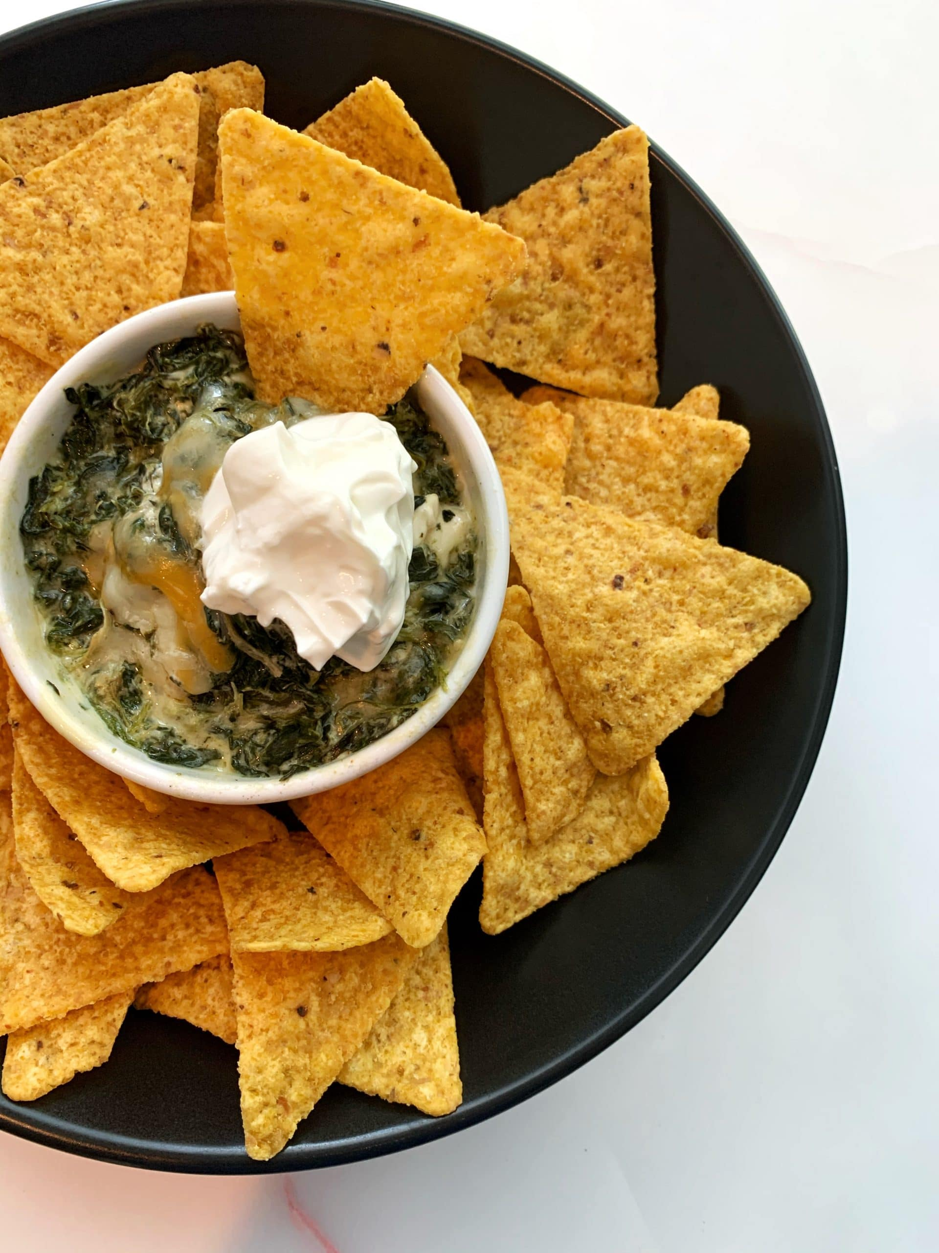 homemade spinach dip in a white bowl surrounded by tortilla chips