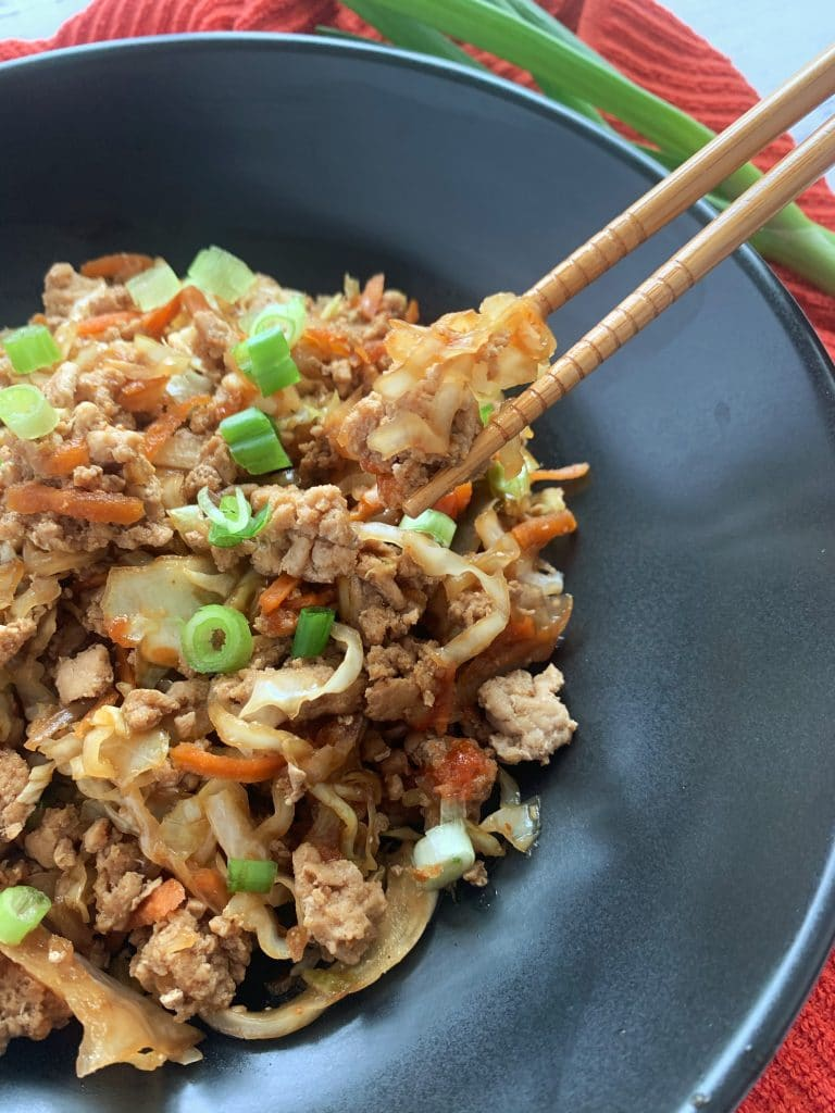 egg roll in a bowl in a black bowl with chopsticks