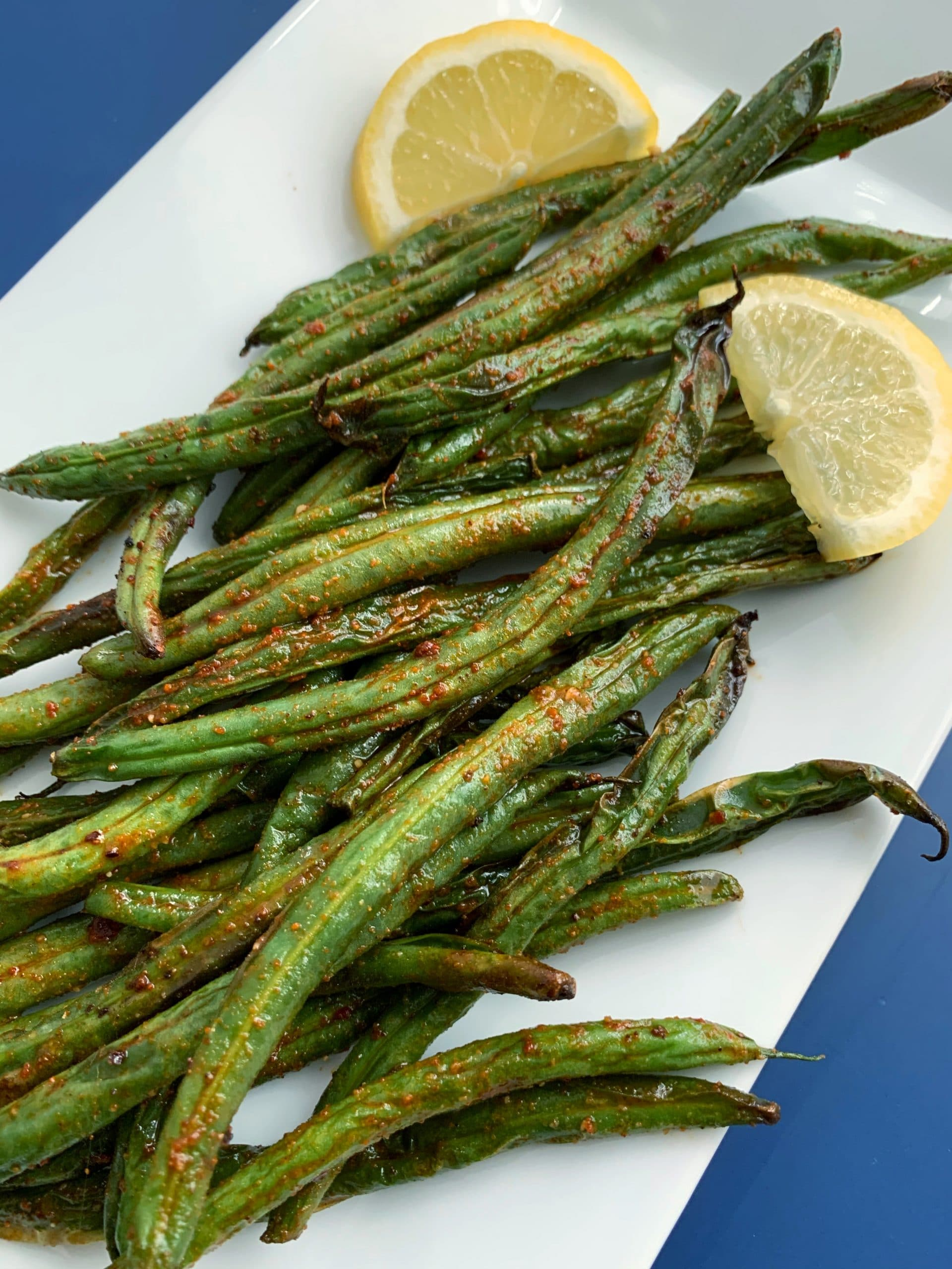 air fried harissa green beans on a white plate with lemon slice