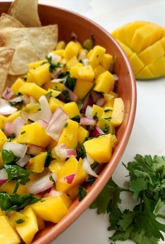 bowl of homemade mango salsa with tortilla chips, cilantro, and a scored mango on the side